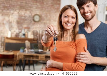 Happy loving couple holding keys of new home. Focus on keys.
