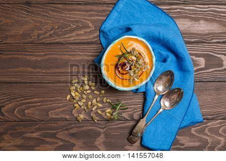 Roasted pumpkin soup with balsamic and pumpkin seeds on wooden background, top view