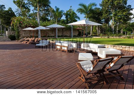 Sun Umbrellas And Wooden Beds Near Swimming Pool