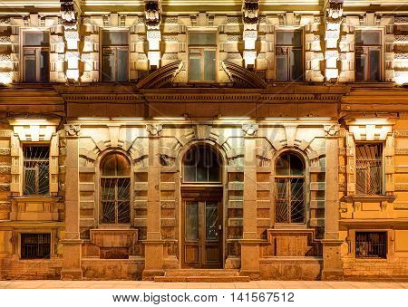 Several windows in a row and door on night illuminated facade of urban apartment building front view St. Petersburg Russia