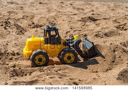Yellow toy shovel on the sand digging bucket