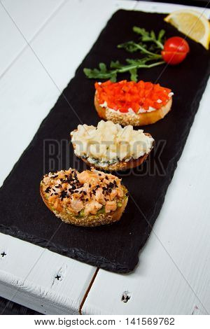 Small Canape, Crostini With Grilled Baguette With Salmon, Pear And Sweet Peppers. Delicious Appetize