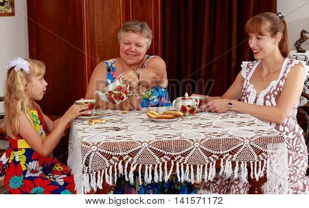 Mother and daughter came to her grandmother to visit. Family sitting at table and drinking tea . retro style.