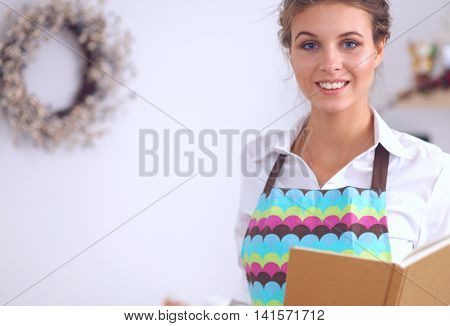 Young woman reading cookbook in the kitchen, looking for recipe, isolated