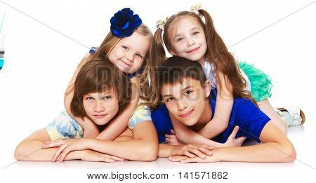 Horizontally elongated rectangular frame. Two little girls sisters lie on top of his brothers and hugging them around the neck. The picture shows 4 children - Isolated on white background