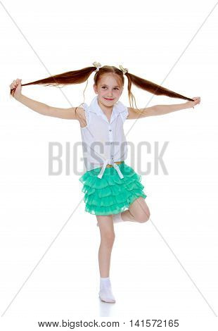 Joyful little girl in a short green skirt and white shirt without any inscriptions . Girl jerks himself off long braids - Isolated on white background