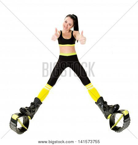 smiling young woman brunette with long hair in a kangoo jumps shoes showing fingers up sign OK. Isolated on white background in studio. Shot at wide angle
