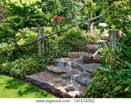 Natural stone stairs landscaping in beautiful lush green blooming home garden