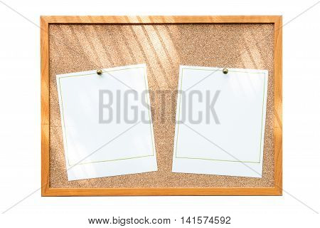 Blank photo frames on cork board with window shadow isolated on white background.