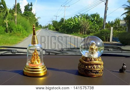 good luck Buddhist statues in glass globes on the dashboard of a car driving through southern Thailand, with banana and coconut trees beside the road ahead