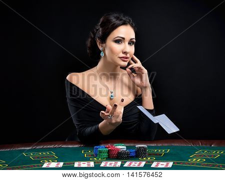 sexy woman with poker cards and chips. Female player in a beautiful black dress