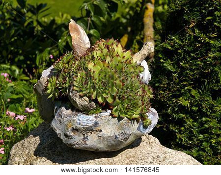Beautiful creative decoration made of stone in a lush green garden