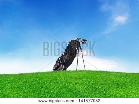 Golf bag on a green meadow with clear blue sky and copy space.