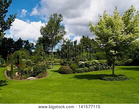 Traditional beautiful landscaped lush green blooming English garden in summer