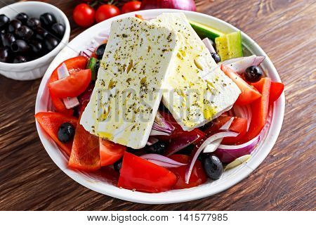 Greek salad with fresh sweet pepper, red onion, orange cherry tomatoes, cucumber, black olives and feta chees drizzled with extra virgin olive oil on wooden table.