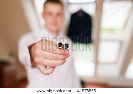 Man puts the cufflinks in a room