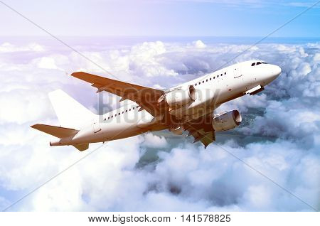 White airplane flying in the sky among white dense clouds floating over land surface. Birds eye view of flying airplane. Closeup of airplane in the sky under sunlight