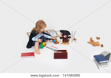 Little boy child blond in black gown sitting playing with toy cars near teddy bear in square hat box with colored pencils diaries notebook wooden cubes school stationery isolated on white background