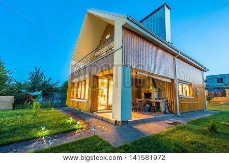 Beautiful wooden house with a lawn. Facade of traditional homes with grass in the foreground. at sunset and sunrise