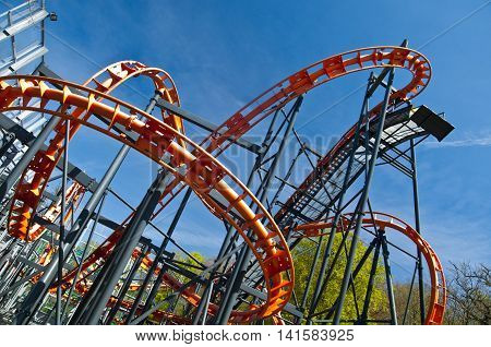 Rollercoaster in a park against blue sky
