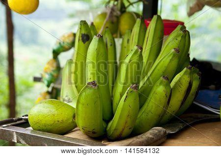 Green bananas and fruits at country marketplace