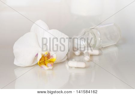 Pills and orchid flower - health and medicine set on white