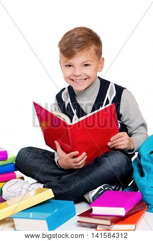 Young male student is sitting on the floor, reading a book. Isolated on a white background. Happy schoolboy with backpack and books - back to school concept.
