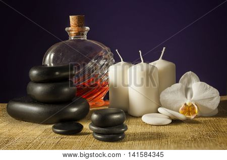 Spa composition on violet background - orchid stones candles