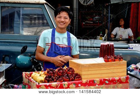 Bangkok Thailand - December 27 2013: Thai man selling freshly squeezed Pomegranate juice from his food cart on Yaoworat Road in Chinatown