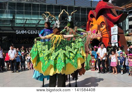 Bangkok Thailand - January 11 2013: A trio of imaginative antelope stilt-walking European women performers entertain crowds in the Siam Paragon & Siam Center outdoor plaza on Children's Day