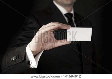Business man in suit showing a blak business card isolated on black