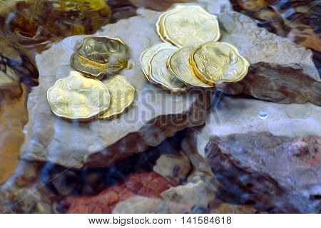 money in the river on the rocks, running out as fast as the water flows, coins under water, waves covered