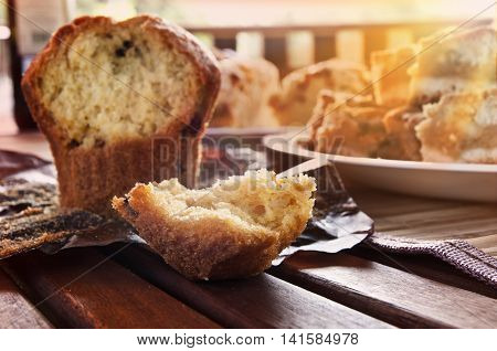 Fresh muffin lying on wooden table in garden