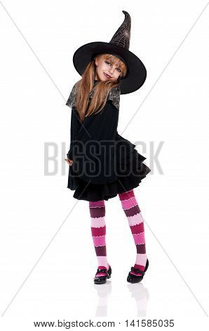 Halloween witch isolated on white background. Beautiful little girl in witches hat and costume - full length portrait.