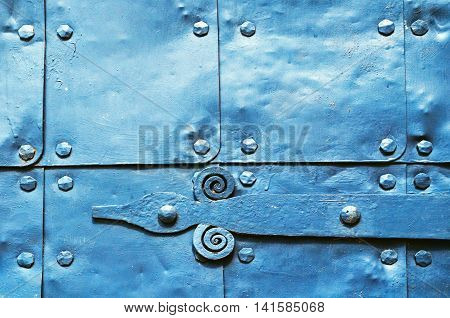 Metal blue surface of old hammered metal plates with metal rivets and architectural details on them. Metal blue industrial background.