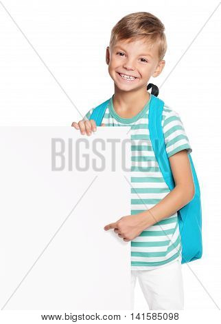 Portrait of happy schoolboy with white blank isolated on white background. Child holding empty placard and looking at camera.