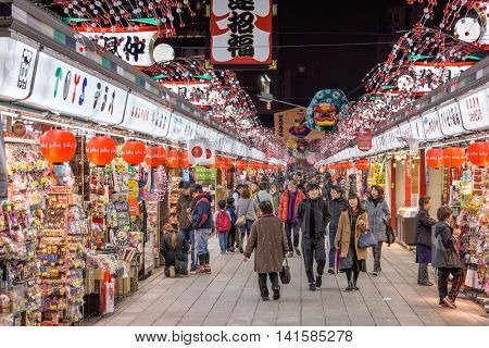 TOKYO, JAPAN - DECEMBER 23, 2015: Visitors to Senosoji Temple walk through Nakamise Shopping Street. The shop lined pedestrian street stretches from the fisrt main gate to the main temple grounds.