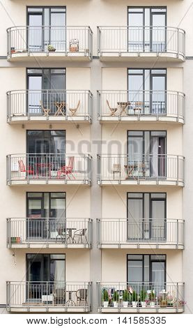 Modern new building with balconies full of flowers, tables, chairs