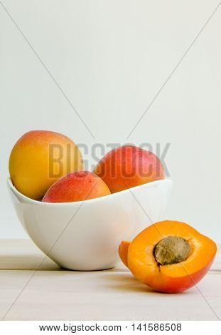 Apricots in white bowl with open apricot.