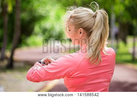 Sports Athlete Runner Woman Looking At Heart Rate Monitor After Jogging