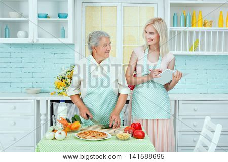 Grandmother tells cooking recipes of the young woman. She is learning to cook in the kitchen.