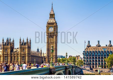 London UK - July 19 2016 - Big Ben and House of Parliament in London with a crowd of tourists on a cloudless day