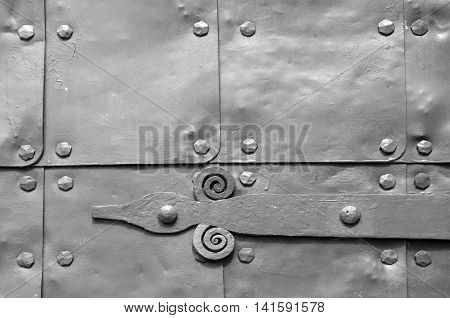 Architecture detailed background - aged wooden door with metal rivets and upper arch of white stone - vintage architecture background