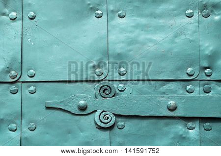 Metal light green background of old hammered metal plates with metal rivets and architectural details on them. Metal bright blue industrial background.