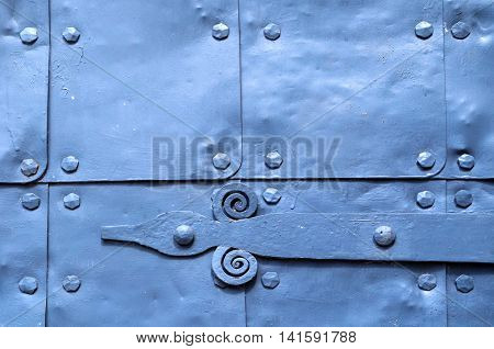 Metal light violet background of old hammered metal plates with metal rivets and architectural details on them. Metal bright blue industrial background.