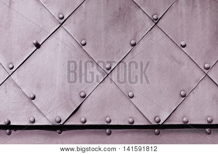 Rough industrial background. Textured metallic surface of aged carved metal plates with small rivets on them -metal background.