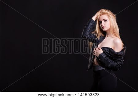 Sexy girl in leather jacket with no bra on her on black background in studio photo. Sensuality and sexuality