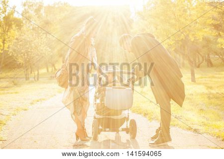 Happy Familly With Their Kid In The Park. Image With Sun Rays Above