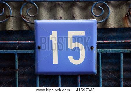 blue square metal number plate with the number fifteen on blue metal bar