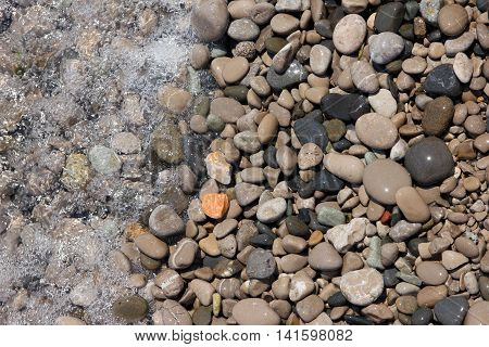 beautiful wet round colored sea pebbles on pebble beach with bubbling sea water closeup